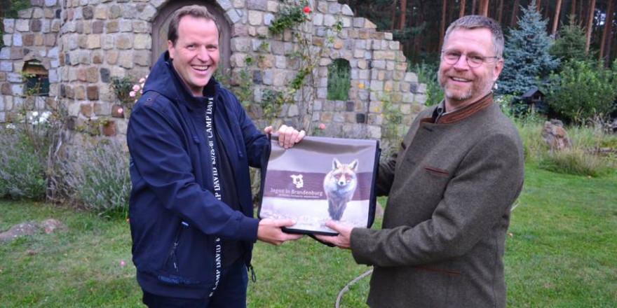 Während der Veranstaltung überreicht Präsidiumsmitglied Jörg Stendel (r.) ein Begrüßungsgeschenk an Frank Neumann, den Vorsitzenden von Rehkitzrettung Brandenburg e.V. (Foto: Hamann/LJVB)