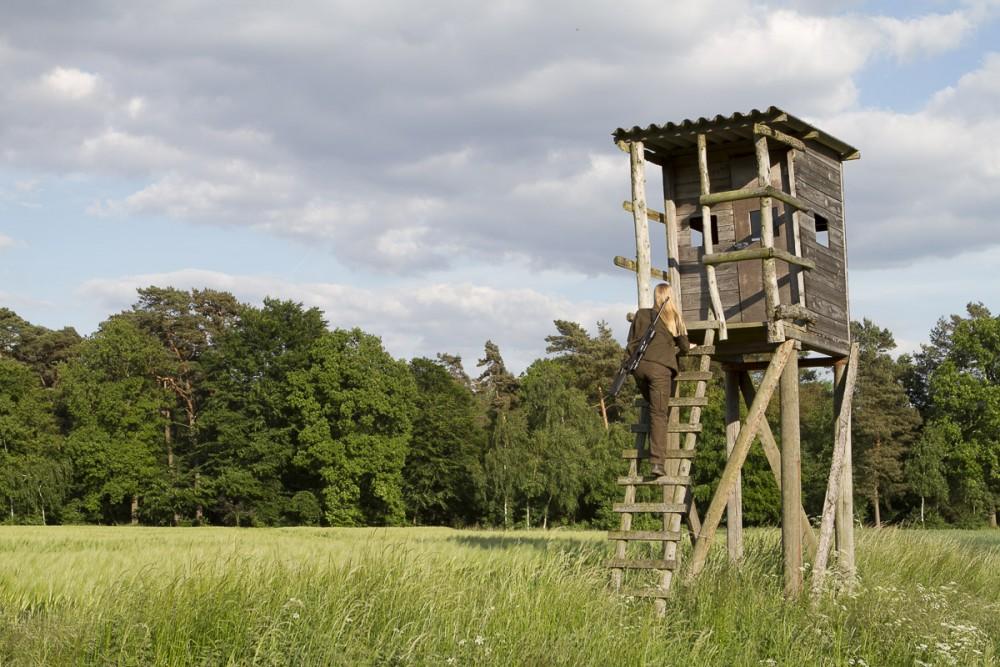 Jägerin klettert auf Hochsitz