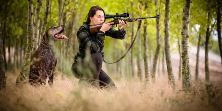 Jägerin mit Hund und Gewehr im Wald (Symbolbild: iStock/ ViktorCap)