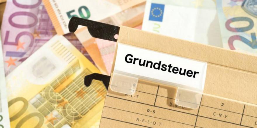 """Bargeld mit einer Akte mit Aufrschrift """"Grundsteuer"""" (Symbolbild: iStock/Stadtratte)"""
