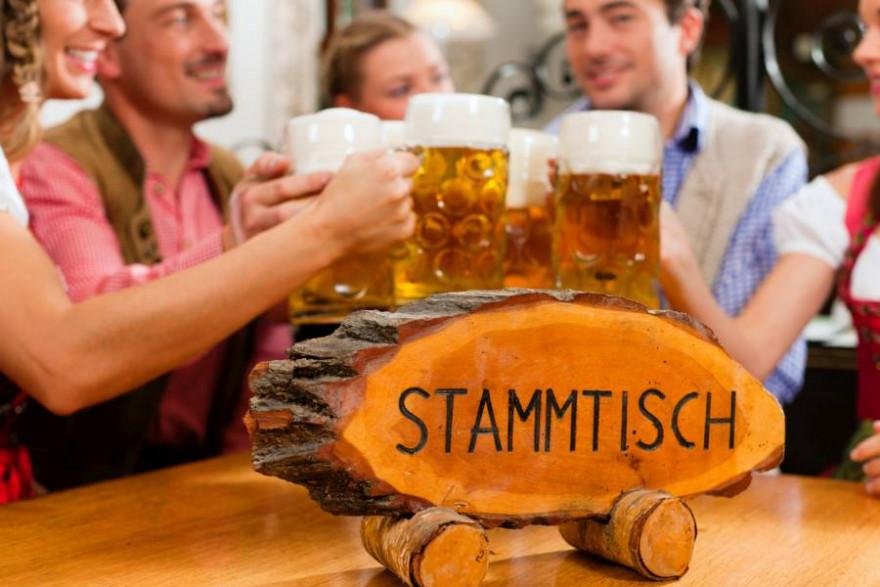 Menschen mit Maßkrügen Bier an einem Stammtisch. (Symbolbild: kzenon)