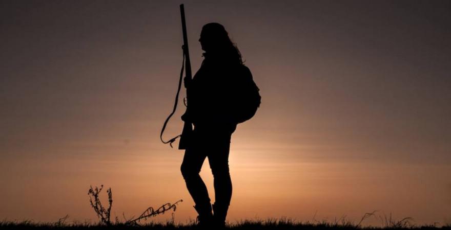 Jägerin mit Rucksack und Jagdgewehr im Abendrot (Symbolbild: rabit023)