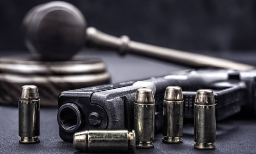 Eine Pistole mit Patronen vor einem Richterhammer (Symbolbild: joebelanger)