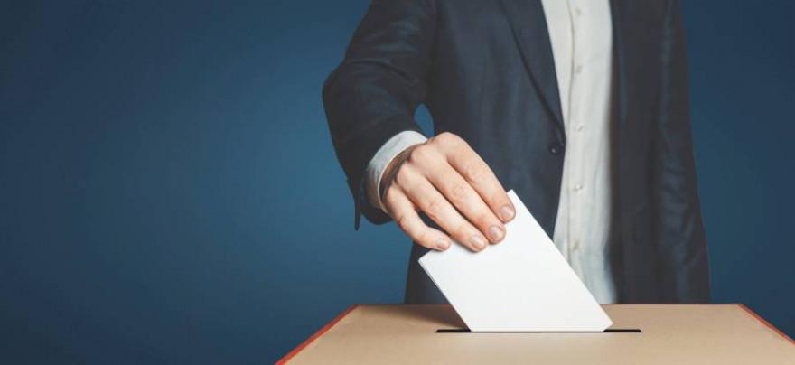 Ein Mann wirft einen Umschlag in eine Wahlurne (Beispielbild: iStock/Sergey Tinyakov)