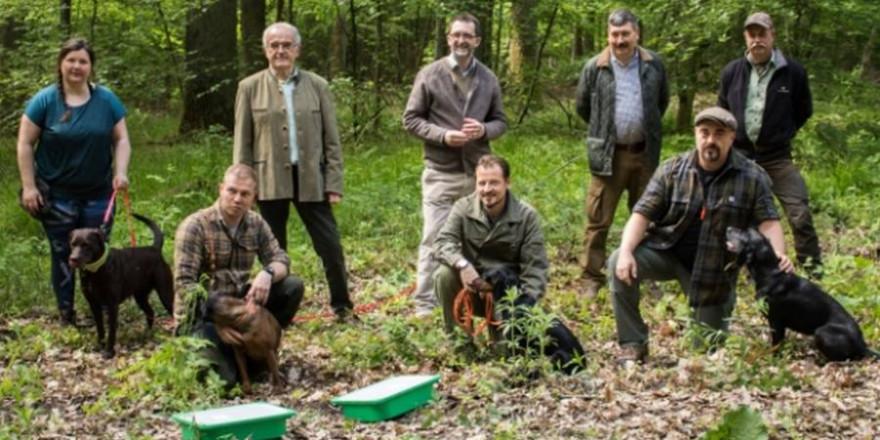 Auf dem Bild sieht man Umweltminister Reinhold Jost mit den auszubildenden Kadaversuchhunden des VJS. (Foto: (c) S. Schorr, MUV)