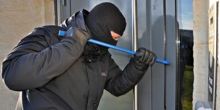 Ein Maskierter versucht eine Türe mit einem Brecheisen aufzuhebeln (Symbolbild: Steffen Salow)