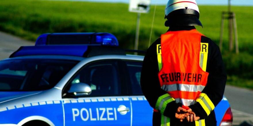 Ein Feuerwehrmann steht vor einem Polizeiauto (Symbolbild: Rico Löb)