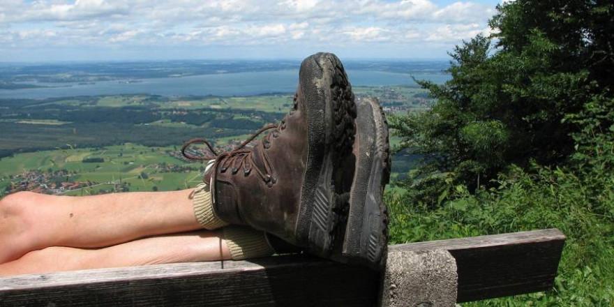 Wanderer rastet auf einer Bank mit Blick auf den Chiemsee (Symbolbild: Marjon Besteman)